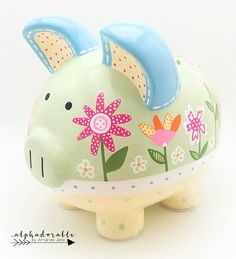 This Daisy Garden Floral personalized piggy bank is created with porcelain ceramic and is completely hand painted using the highest quality acrylic paint. The art is forever protected by a glossy diamond finish glaze. Each piggy bank is hand painted especially for you on an individual