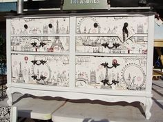 Painted white with black trim and finished with s super-cute Paris themed wall-paper on the front of the drawers