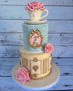 This cake was for an English tea time themed bridal shower. Roses and tea cup/saucer were made of gumpaste. Bottom tier was inspired by decorative wood paneled walls. Top tier is covered with the rose mat by sugar veil.