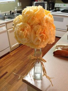 Fall in love bridal shower theme. Coffee filter flowers dyed with orange food coloring, $1 vase and $1 raffia from dollar tree. Centerpiece about $3 to make. Instead of styrofoam ball I crumpled up magazine pages into a ball & taped it with masking tape.