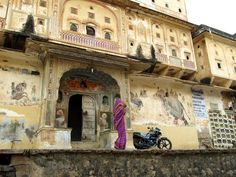 A sari-clad lady passes a painted haveli in Samode, Rajasthan.