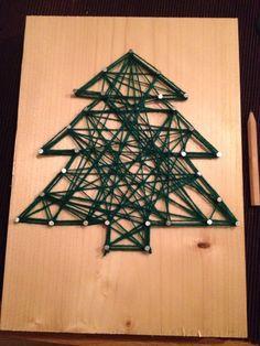 Kerstboom gemaakt van spijkers en wol op een houten plank