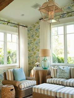 beachy cottage design with green & blue floral wallpaper, lantern, woven seagrass chairs sofa and ottomans with white & beige striped cushions, recycled turquoise blue glass lamp, round burlap skirted table and white sheers