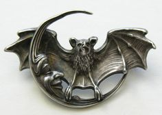 Unger Bat and Man in the Moon Sterling Brooch  This  very hard to find Unger brooch features a bat with outstretched wings and a smiling man in the moon.  The brooch measures 2 7/8ths inches by  1 7/8ths inches and is marked UB (Unger Brothers), 925 fine sterling, and copyright 1904