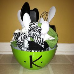 Wedding shower gift: Use Kitchen towel with ribbon hot glued around, then fan dish cloth out, and then put utensils down inside with a bow tied to spoon. Last initial the bowl with paint pen