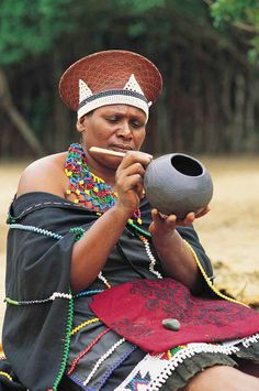 A married Zulu woman wearing a traditional hat, cloak and necklace is painting a pot. South Africa A married Zulu woman wearing a traditional hat, cloak and necklace is painting a pot. Zulu Women, African Women, African Art, African Fashion, We Are The World, People Of The World, South African Tribes, Safari, Art Tribal