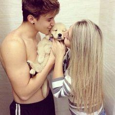 pareja joven besando cachorro