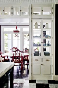 Gorgeous Kitchen. Love the White Cabinetry with the see thru glass cabinets & love the Black Island, the black & white flooring & the Red Dining Chairs. Creating a Chinoiserie Chic Kitchen