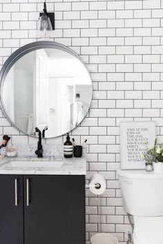 The white subway tile walls with black grout provide a distinctive lighter look for this bathroom without windows