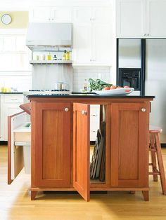 This compact-but-capable cherry island provides additional work space and cabinetry storage space for a small kitchen. It features vertical storage for baking pans and sheets and a handy rollout recycling bin. On the opposite end, a stool tucks under the counter for a small work spot. Tilt-down drawer fronts hide electrical outlets necessary for baking equipment.