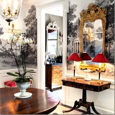 The main rooms of the 1930s Chicago apartment are arranged off the large entry hall.  Here, Branca introduces the color scheme:  gray, red, gold, and black.   A beautiful Zuber wallpaper lines the upper walls.