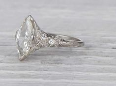 Antique Edwardian engagement ring made in platinum and centered with an approximately 1.20carat EGL certified marquisecut diamond with G-H color and VS2 clarity. Circa 1915 Lovely Edwardian features in this low profile engagement ring featuring a marquise cut. Marquise cuts always appear larger then other cuts becaus