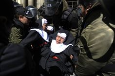 Members of the Mujeres Creando (Women Creating) activist women group dressed as nuns who were protesting against the upcoming visit of Pope Francis to Bolivia, are taken away by police in front of the Metropolitan Cathedral in La Paz, on July 6, 2015. Pope Francis, in South America on a three-nation tour, will perform mass in Ecuador Monday, with more than a million faithful — many of whom camped out overnight — expected to attend.