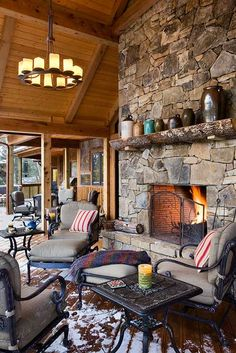 This deck space offers several covered areas framed in western red cedar for al fresco entertaining. Opening off the living room, the main porch offers an outdoor fireplace of native stacked stone and a candle chandelier for a cozy feel in any weather. Photo by Roger Wade.