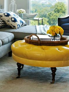 This yellow leather footstool becomes the focal point in this grey/blue inspired room!