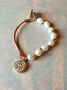 Like - One side pearls - the other plain. Prefer a cross or heart medallion. Pearl and Leather Bracelet with St. Benedict by SunnyDsMarket, $24.00