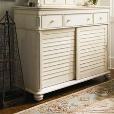 Finished in a weathered linen hue, this classic wood dresser pairs country-chic style with versatile design. Sliding louvered doors and 6 drawers easily stow clothing and accessories, while an included power outlet and audio player storage keep your favorite music at the ready.   Product: DresserConstruction Material: WoodColor: LinenFeatures: Part of the Paula Deen Home CollectionTwo large sliding doorsSix drawersTop center drawer has drop front and power outlet Distressed ...