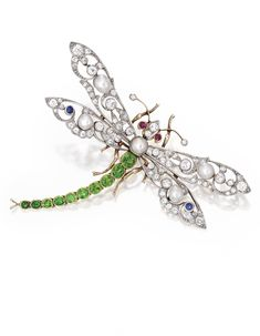 GOLD, PLATINUM, DEMANTOID GARNET, PEARL AND DIAMOND BROOCH. Designed as a dragonfly set with ten oval-shaped demantoid garnets weighing approximately 2.50 carats, centered by a cultured pearl measuring approximately 6.5 mm, the wings accented by four natural pearls measuring approximately 5.6 to 5.3 mm and two round sapphires, further set with old European-cut diamonds weighing approximately 2.85 carats and two round ruby eyes, numbered 5081, fitted with pendant loop; circa 1900.