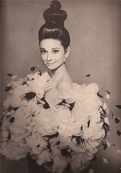 Audrey Hepburn in Saint Laurent's fluttering evening hug: a giant puff of organdie petal and feather flowers bubbling over with Parisian gaiety. Harry Winston jewels, Alexandre of Paris coiffure