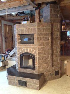 Granite masonry heater with black oven.
