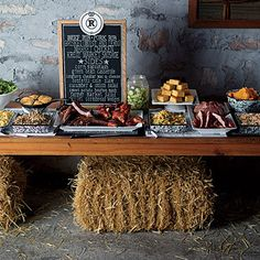Great food display for rehearsal dinner.  Could use an old door, barn door, gate, fencing on hay bales.