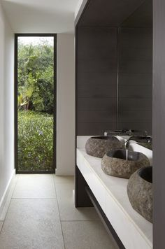 Beautiful stone basins in this sleek, minimalist bathroom