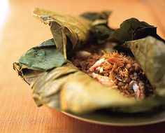 Fook Lam Moon Wan Chai Hong Kong Steamed lotus leaf rice  Fried rice with crab meat, conpoy, diced duck and mushrooms wrapped in fresh lotus. Delicately fried with all the associated ingredients, the rice is encased in a large lotus leaf before steaming. Nuances of the fragrant lotus leaf are fully infused into the rice.