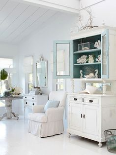You could find an old cupboard to redo to look like this. - Although predominantly painted soft white, the interior of the doors of the hutch were painted a faded hue of blue, signifying the ocean. bhg