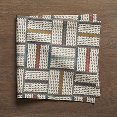 A playful grid patterns grey tones with pops of bright orange, teal and yellow on this eye-catching cotton dinner napkin.