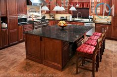 This kitchen features Tan Brown granite on both the large island and the main counters, a perfect match to the wood finish.