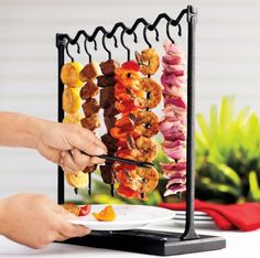 Skewer Station ~ a dramatic way to present grilled skewers of a single ingredient. Grill different meats and vegetables, then hang for serving. Simply push meat or vegetable from skewer with the included cast-iron fork onto a plate held underneath. The grooved wooden tray prevents juices from spilling onto your table.