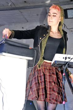 Grimes wears a plaid skirt with a green sweater, and military-inspired jacket for her performance at Islington Mill in Manchester, England.   - ELLE.com
