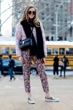 winter outfit - Chira wearing pink floral pants, gold slip on shoes, a trendy pink fuzzy coat with black scarf and crossbody bag