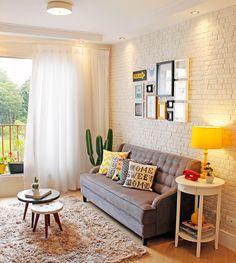 Quadrinhos, almofadas, um cactus e um abajur amarelo vibrante colorem esta sala de estar de mobiliário de tons sóbrios.