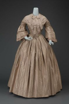 Finely striped silk, probably American, ca 1840-1860. High bodice, fan front, vee point; open sleeves, double at the opening, triple puff at armscye; pleated skirt. At throat, self fabric bow and pinked tails. MFA BOSTON