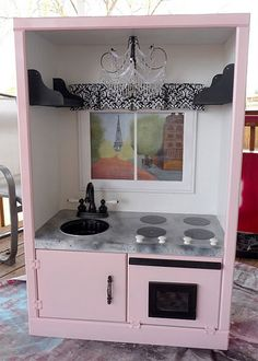 Turn an entertainment center into a great play kitchen~ Love the chandelier!
