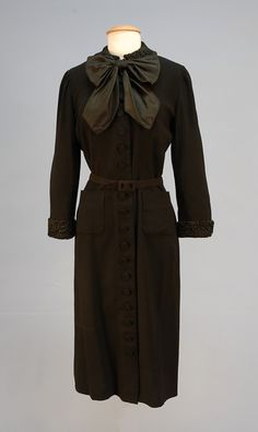 c. 1950.BLACK WOOL CREPE DRESS with FUR TRIM,  Long sleeve with black Russian lamb collar and cuff, black taffeta neck tie, center front self buttons to hem, self belt above patch pockets.