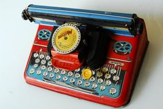 tin typewriter toy - you had to twist the dial to the letter you wanted and then hit the large red tab under the dial and it printed.  No real keys.
