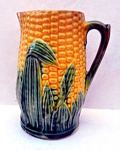 Majolica Corn Pitcher Antique Primitive, Cottage Kitchen Creamer Vase  • Beautiful bright color on this early English corn pitcher. It's unmarked other than having three brush marks on the base. A picture-perfect pitcher for adding a splash of color.  • Measures 4.5 tall x 3-1/4 from spout to back of handle. • Very good condition for majolica of this age with only a couple of small nicks and a tight interior hairline.   To view more Cottage and Camp items Click here: https://ww...
