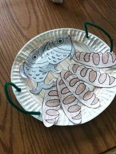 paper plate basket for Jesus feeds the 5,000. fish and bread printable - http://craftingthewordofgod.com/2013/04/09/feeding-the-5000/ Preschool age - we are coloring the pictures and gluing them to the basket