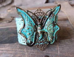 Turquoise upcycled leather cuff features a beautiful butterfly charm, hand-aged with a verdigris patina. Handmade artisan recycled jewelry.