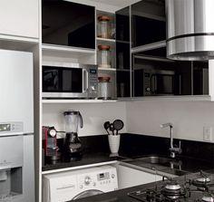 """Roupa suja se lava na cozinha: repare que a máquina lava e seca (modelo Prime touch de 8,5 kg, da LG. R$ 2320,26, na Fastshop) com abertura frontal encaixa-se sob a bancada, ao lado da geladeira. O teto, rebaixado em toda a extensão, não só embutiu a iluminação como também permitiu instalar a coifa. Puxou-se a tubulação até a lateral do prédio a fim de expelir lá fora o ar sugado. """"Em imóveis tamanho P, o aparelho é essencial"""", defende a arquiteta Marcella Bacellar. Projeto feito em…"""