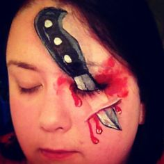 Face paint Halloween. Knife stab adult boys painting