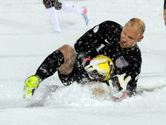 U.S. goalkeeper slides in the snow to make a save in the second half.
