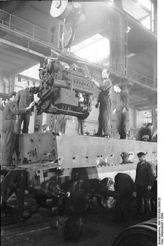 Factory workers at a Henschel Factory installing the torsion bars while other technicians install the Maybach engine
