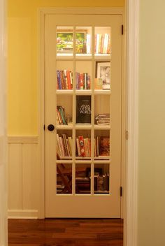 Turn a closet into a library and add a French door. Love the way this looks!!