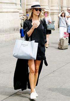 Rosie Huntington-Whiteley wears a black top, shorts, a black trench coat, white sneakers, a pastel Balenciaga bag, fedora, and Dior sunglasses