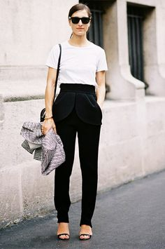 White t-shirt tucked into black high-waisted trousers, and black ankle strap heels