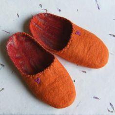 Zapatillas de estar en casa de fieltro hecho a mano a partir de lana merina, con un botón en forma de corazón. Muy suaves y cómodas, porque están hechas de una sola pieza, sin costuras. La suela es de latex pintado, para que no resbalen.