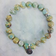 The Kundalini Mala Bracelet is made from 21 serpentine mala beads. It is completed with an antiqued OM. Yoga bracelet for spiritual awakening.